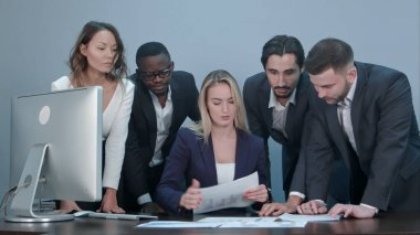 Group of business people busy discussing financial matter during meeting, standing around female boss desk