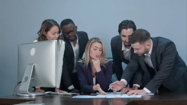 Group of multiethnic diverse young business people in a meeting standing around a table with serious expressions discussing a new strategy or solution to a problem