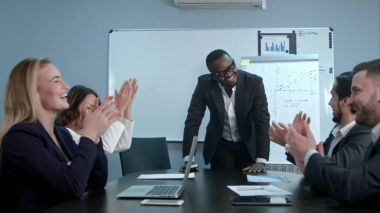 Multi ethnic business group greets afro-american boss with clapping and smiling