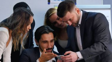 Smiling business team working with smartphone, watching somethng interesting in office