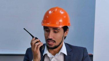Businessman in helmet talking at radio set sitting in office