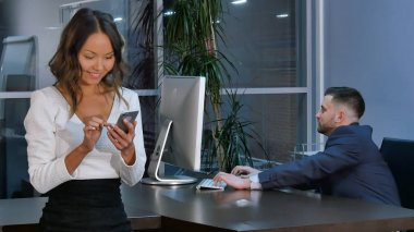 Businessman working on laptop, businesswoman using smartphone in office