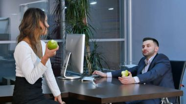Two office workers having a break, aeting green apples and talking in office
