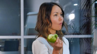 Pretty businesswoman eating green apple in the office