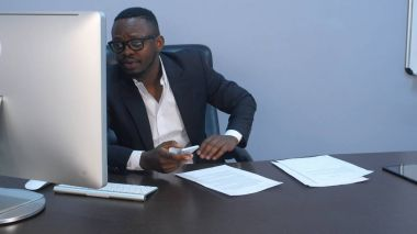 Afro-american businessman texting emails on his smartphone indoors