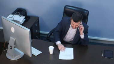 Businessman talking on phone and working on computer in office