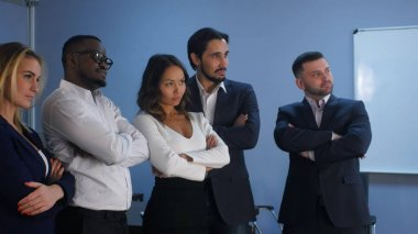Business team standing with serious look in office
