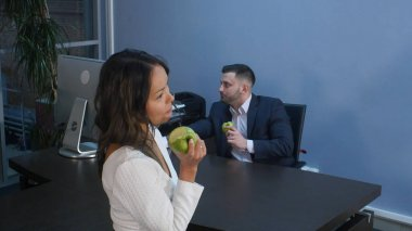 Young business people having lunch together, eating green apple