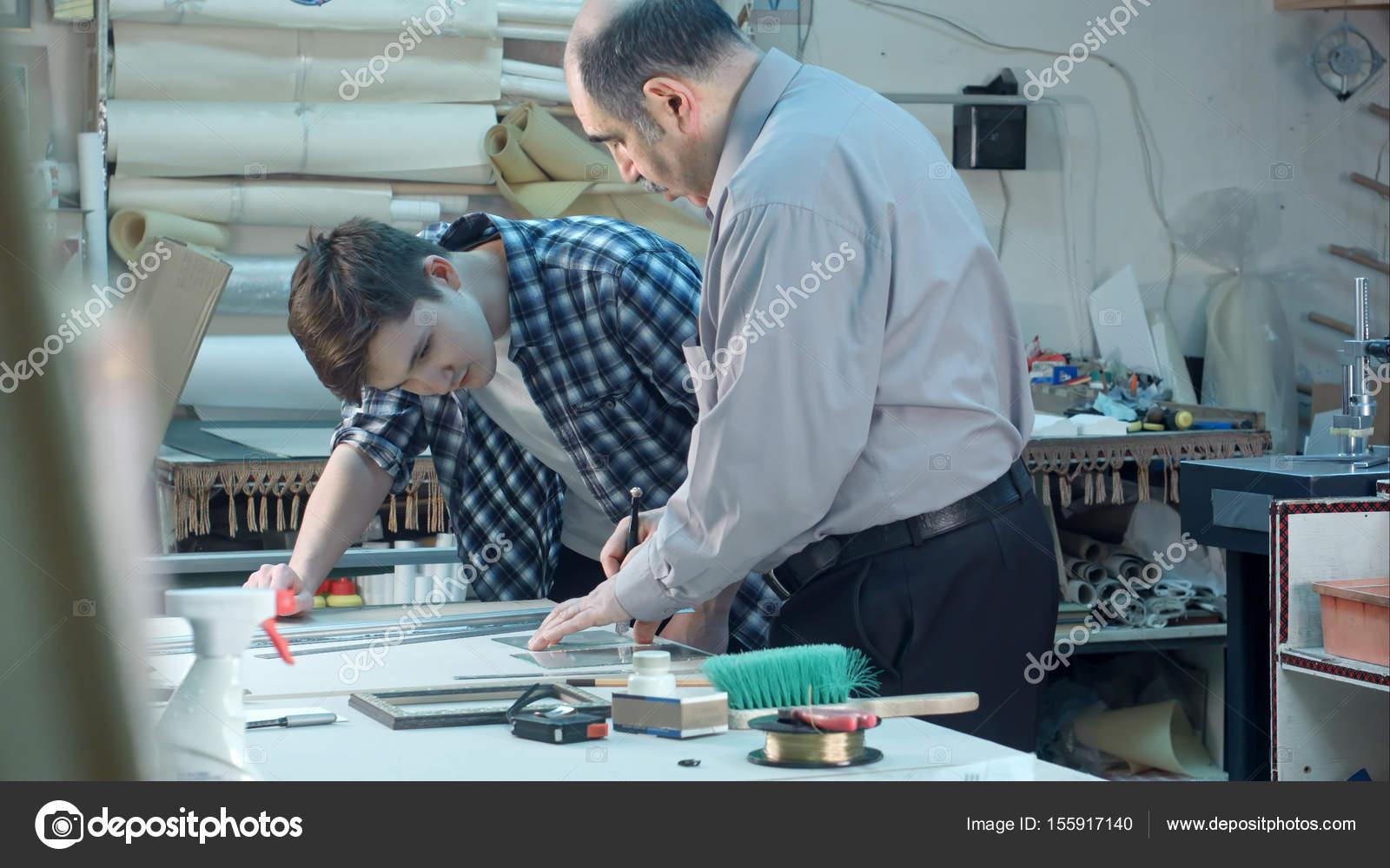 Trabajador de sexo masculino Senior instruir a la joven aprendiz ...