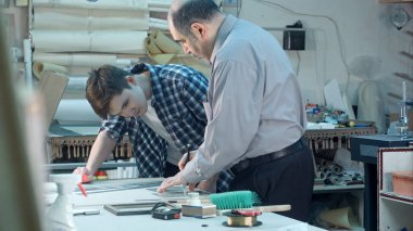 Senior male worker instructing young trainee how to cut a glass for frame behind the desk in frame workshop