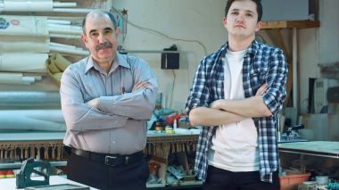 Portrait of two workers, standing in workshop and looking at camera seriously