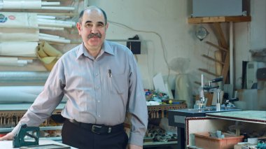 Portrait of a senior male business owner behind the counter of his workshop, standing and smiling to a camera