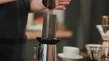 Barista adding grinded coffee and pouring hot water
