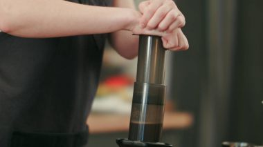 Barista preparing black coffe with aeropress