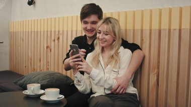 Happy couple using smartphone together and laughing in cafe