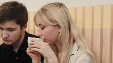 Portrait of young couple talking seriously and drinking coffee at a coffee shop