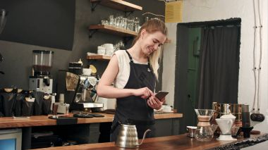 Cheerful and content female barista using mobile phone and texting at coffee shop