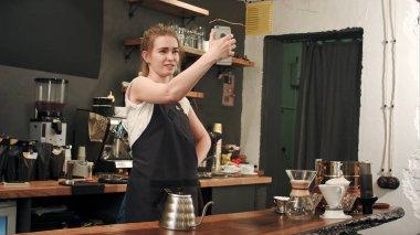 Cheerful female barista using smartphone to take selfie in coffee shop