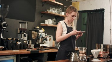 Female barista taking pictures of prepared cofee with smartphone