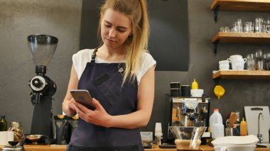 Delighted female barista using cell phone at work place