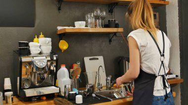 Young female barista washing dishes at workplace