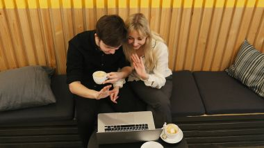 Happy couple having online conference on laptop in a restaurant