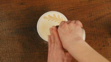 Barista preparing cappuccinno latte art coffee in to white cup