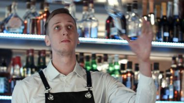 Young professional barman in action with shaker and bottle making cocktail drinks