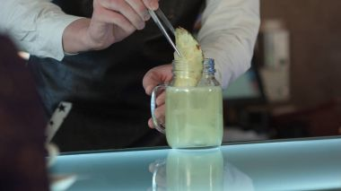 The barman at the bar makes cocktail with ice, decorating with a piece of pineapple