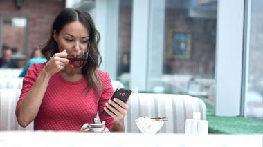 Asian woman looking at cellphone and drinking tea in cafe