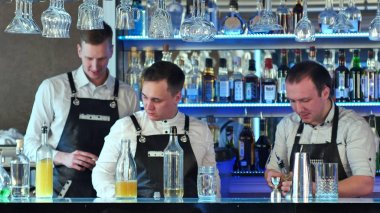 Three bartenders serving cocktails and working in a classy bar