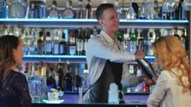 Barman making cocktail for young female friends at the bar