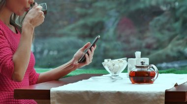 Woman using mobile phone and drinking tea in cafe