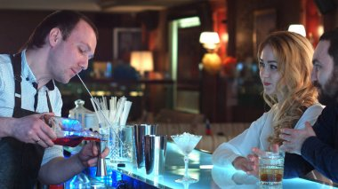 Bartender pouring mixed cocktail for clients in a bar