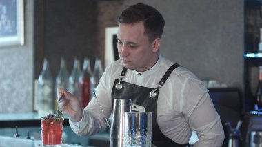 Bartender making and decorating cocktail