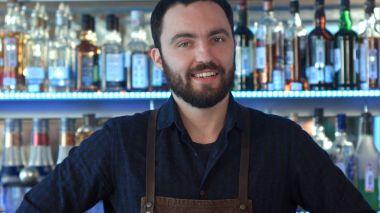 A barman at work smiling and looking at camera
