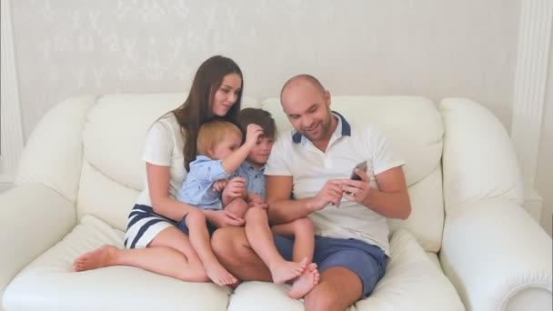 Šťastní rodiče a jejich malé syny na telefonu při pohledu na fotografie