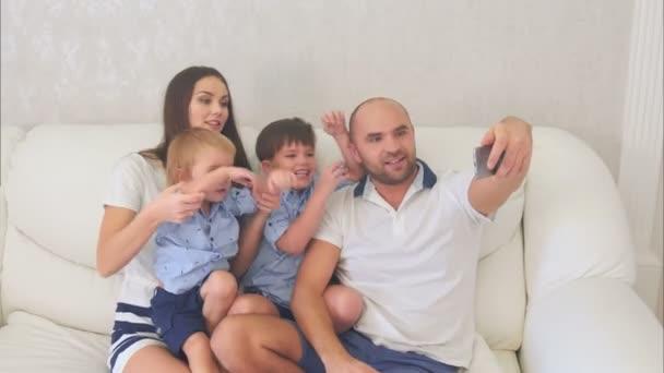 Usmívající se rodina s legrační selfies sedí na pohovce