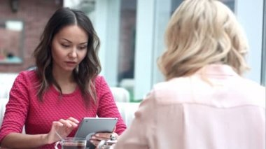 Two young business women sitting at table in cafe, using digital tablet