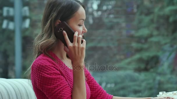 Young charming woman calling with cell telephone while sitting alone in coffee shop during free time