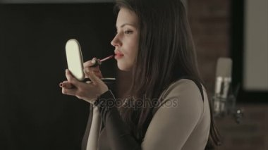 Bautiful young female singer applying lips makeup with cosmetic brush