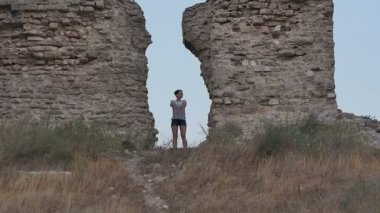 Carefree woman traveler doing funny dance near ancient walls