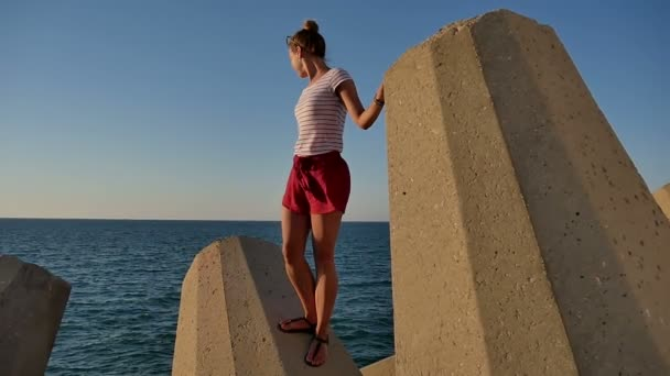 Pretty girl standing on stony blocks looking at the sea