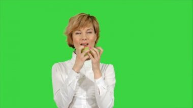 Portrait of young woman eating green apple on a Green Screen, Chroma Key