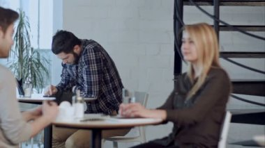 Worried young man using tablet computer in cafe, sitting alone