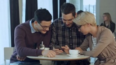 Group of young creative people wearing business casual clothes collaborating at meeting table and discussing work, using smartphone