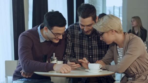 Skupina mladých kreativních lidí nosí ležérní oblečení obchodní spolupráce na jednací stůl a diskutovat o práci, pomocí smartphonu