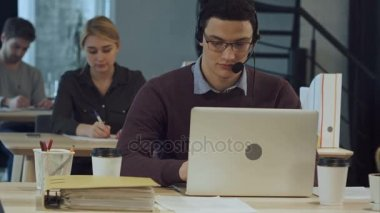 Happy cheerful young worker of call center in head-phones smiling and working on laptop