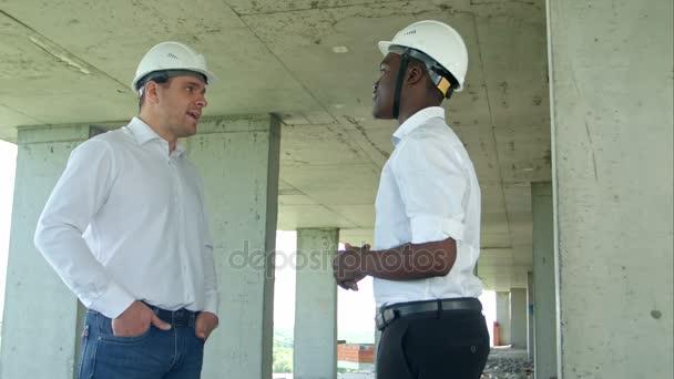 Hezký stavebních podnikatelů v ochranné přilby a vesty s třesoucíma se rukama na staveništi
