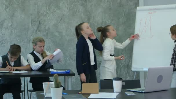 Kids working hard in office, discussing serious problems together, using flipchart